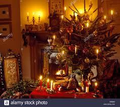 lighted candles on christmas tree and on small table beside lighted candles on christmas tree and on small table beside fireplace in cottage living room