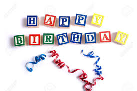 birthday ribbons the words happy birthday spelled out in wooded block on a white