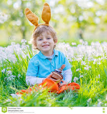 little kid boy with easter bunny ears and cupcake stock photo
