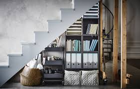 awkward no more that space under the stairs home office supplies are stored under a staircase in a basket a trolley and