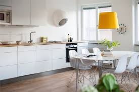 elegant white kitchen ideas with dining table and yellow hanging