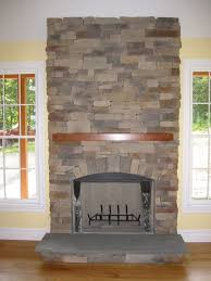 grey stone fireplace with brown wooden mantel and black metal fire