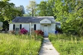 front vew of unmowed lawn of an abandoned foreclosed cape cod