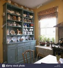 blue green dresser with crockery on shelves in traditional kitchen