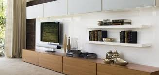 wooden pattern tv cabinet with black hdtv and wall bookcase on the