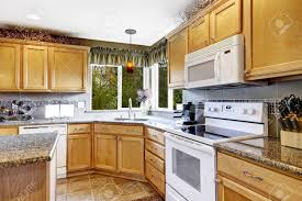 brown kitchen cabinets to white bright kitchen room interior with tile floor light brown storage