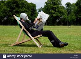 businessman wearing a gas mask whilst seated in a deck chair