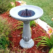 cement bird bath fountain backyard with red mulches and solar bird