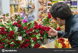 florist shop handsome choosing roses at a florist shop for his