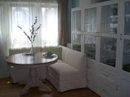 banquette with round table small white slip covered corner banquette seating and round pedestal