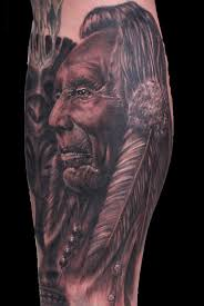 grey native american portrait and feather tattoos on leg in 2017