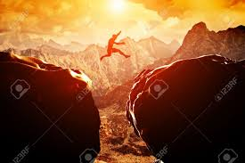 Challenge Success Jumping Precipice Between Two Rocky Mountains At Sunset