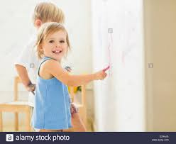 children 2 3 painting on wall stock photo royalty free image