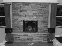 curved black fireplace with gray stone mantel surround built in