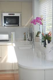 compac moon white quartz worktops with cream kitchen cabinets