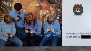 distracted family poses for best christmas card ever image