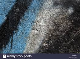 black and blue graffiti on a grainy concrete wall abstract stock