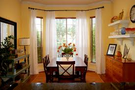 yellow wall paint with bay window also white sheer curtain also