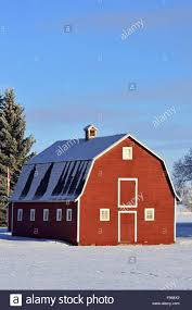 a vertical winter landscape image of a red barn on a farm in rural