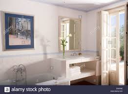 Bathroom In French by Basin In Simple Vanity Unit Beside French Doors In Modern White