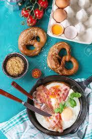 cuisine avec des oeufs petit déjeuner avec des oeufs au plat et bacon dans une poêle en