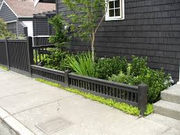 showy horizontal wooden fence in front yard with small garden