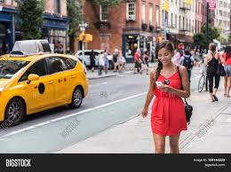 New York Street Map App by Woman Walking In New York City Using Phone App For Taxi Ride