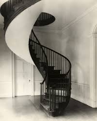black metal spiral staircase with brown wooden tread connected by