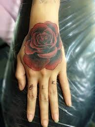 traditional red rose tattoo on hand