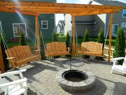 outdoor swings and wooden chairs plus a wooden roof in the yard