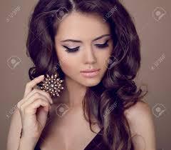 bella donna con i capelli ricci e la sera make up gioielli e
