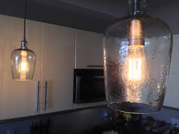 a simple but elegant glass pendant with an edison bulb gives the kitchen a new vibe