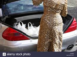 woman in leopard animal print coat loading boot of mercedes car