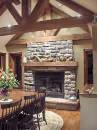 stacked stone fireplace with tv above decorating a mantel with a