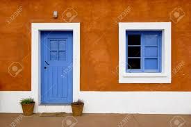 beautiful and funny orange house with blue doors and windows stock