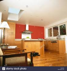 red modern kitchen parquet flooring in modern kitchen extension with red wall and