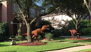 dinosaurs overrun front lawn in neighborhood as t rex and