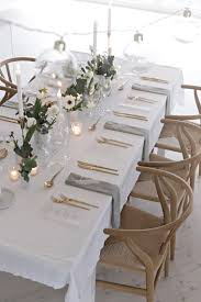 white vases on a white tablecloth gold flatware collection of