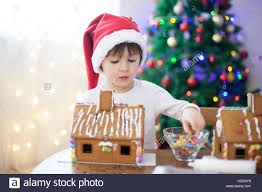 cute little boy making gingerbread cookies house decorating at