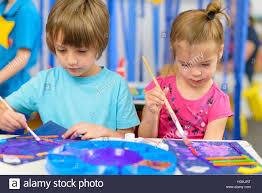 cute kids doing their craft painting at kindergarten stock photo
