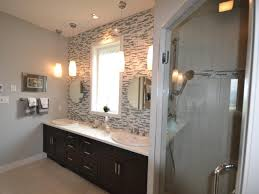 warm lamp mirrored glass tile backsplash with black cabinet on the