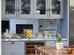 marble worktop wooden dining table glass chandelier blue cupboard