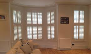 very traditional central tilt rod tier on tier wooden shutters in