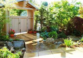 tropical front yard landscape design with wood gate and a pond