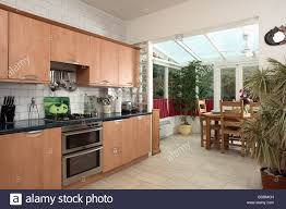 Modern Conservatory Fitted Wood Units In Modern Kitchen With Beige Ceramic Flooring
