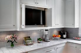 black tv in the white kitchen cabinets along with marble