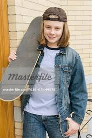 long haired skater boys caucasian boy standing with skateboard stock photo masterfile