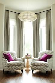 bay window decorated with chairs and table with neutral curtains