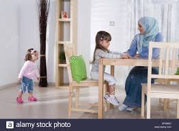 arab mother with two daughters playing at the dining room stock