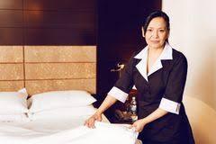 la femme de chambre femme de chambre d hôtel faisant le lit d invité photo stock